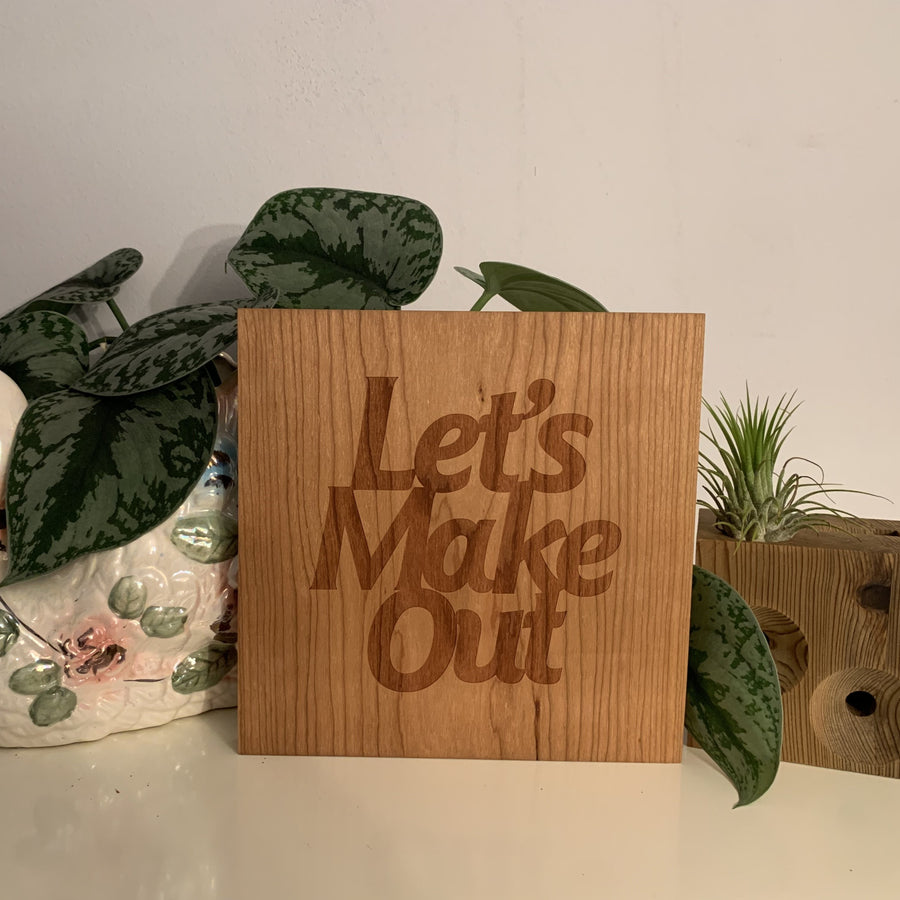 vintage swan planter beside standing laser etched square piece of wood with the words let's make out