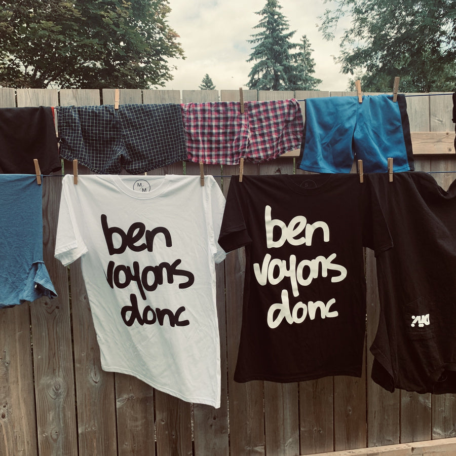 image of a clothing line with white ben voyons donc tee shirt with black lettering and black ben voyons donc tee shirt with white lettering hanging from the line surrounded by other clothing