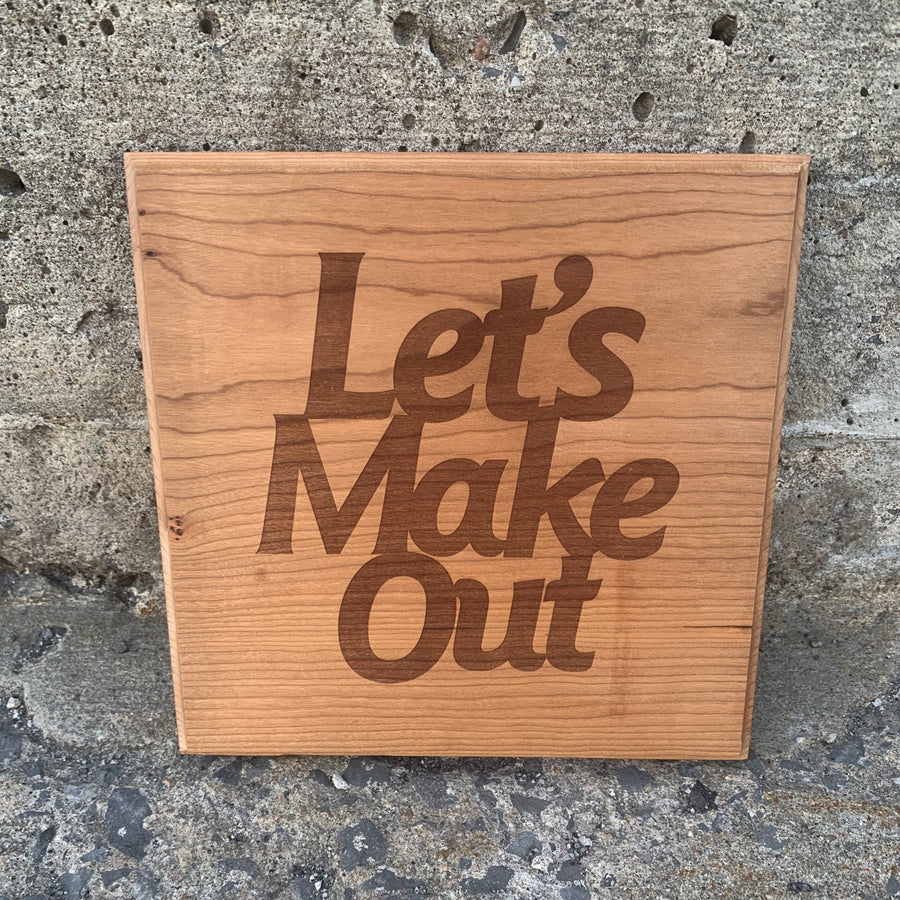 square piece of wood with the words let's make out laser engraved leaning on a concrete wall
