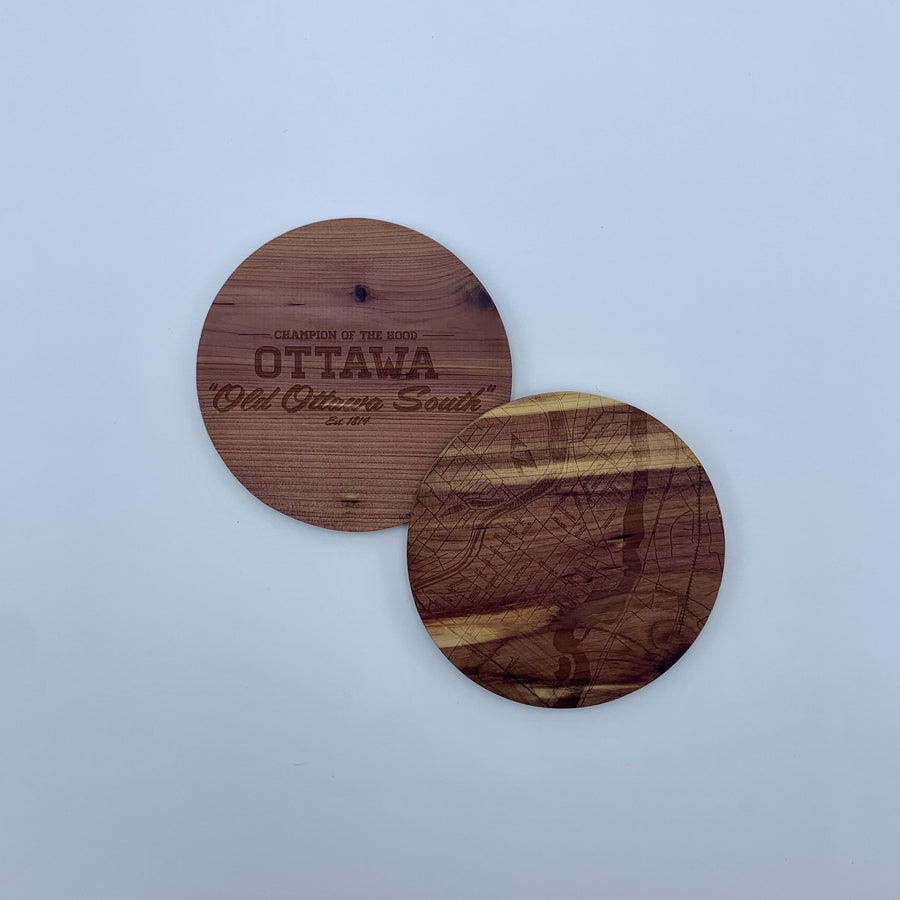 laser etched wood coasters side by side. one of the coasters has a map etched on it, the other one has the words champion of the hood ottawa old ottawa south.