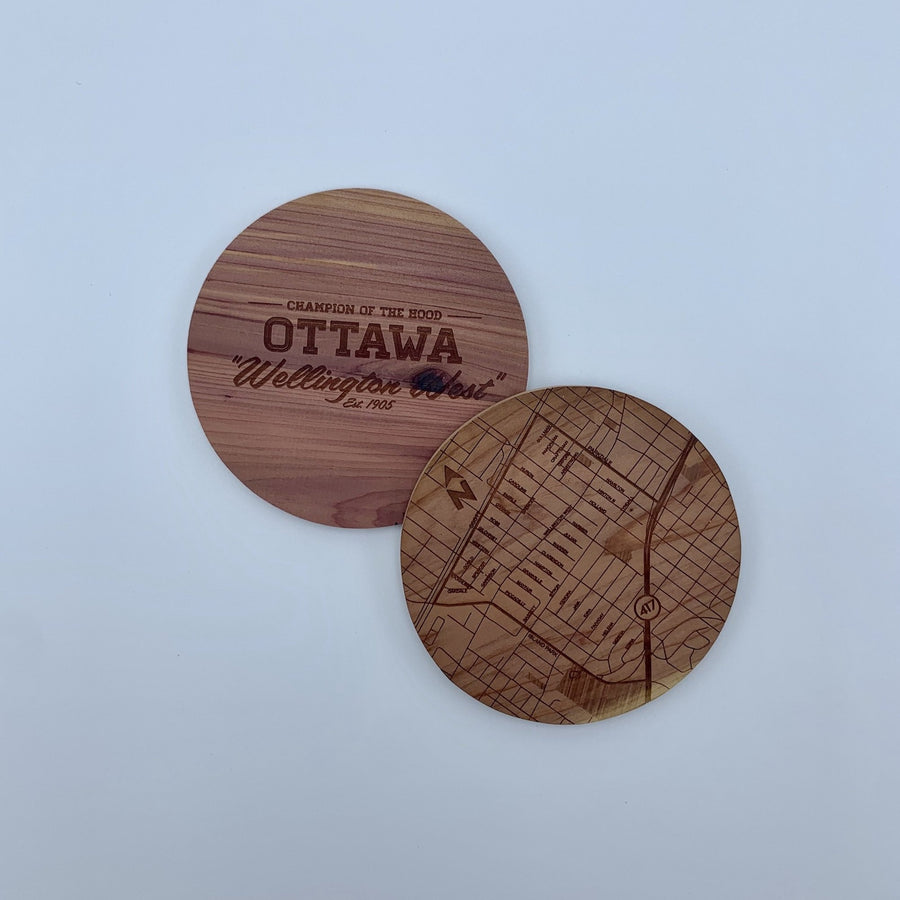 laser etched wood coasters side by side. one of the coasters has a map etched on it, the other one has the words champion of the hood ottawa wellington west.