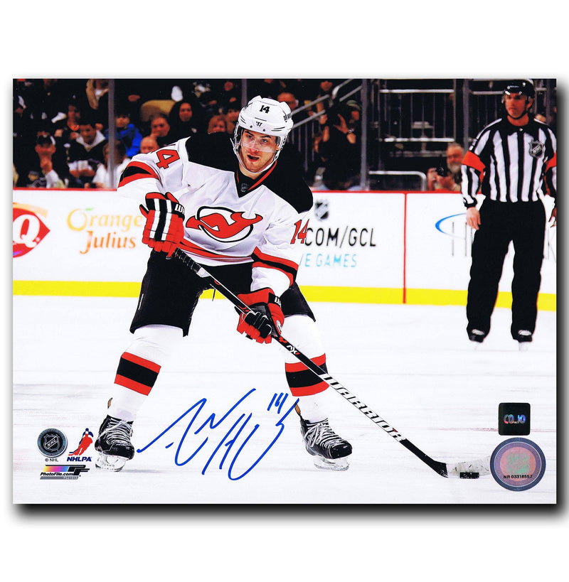 Autographed photo of Adam Henrique in a white New Jersey Devils jersey carrying the puck