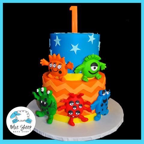 blue, red, and orange 1st birthday cake featuring funny monsters