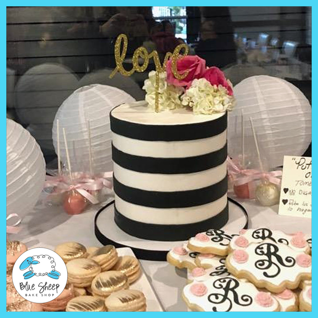 Buttercream cake with black fondant stripes and fresh flowers.