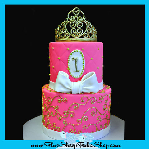 pink and gold princess cake with gold scroll work gold crown bow and quilted pattern