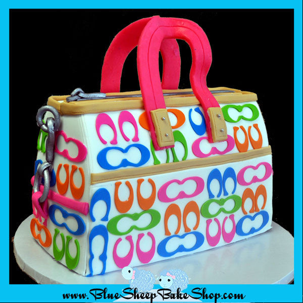 rainbow coach purse cake - cake carved to look like a purse with bright pink, orange, green, and blue c cutout's