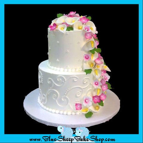 classic butter cream buttercream wedding cake with cascading calla lillies and magenta hydrangea