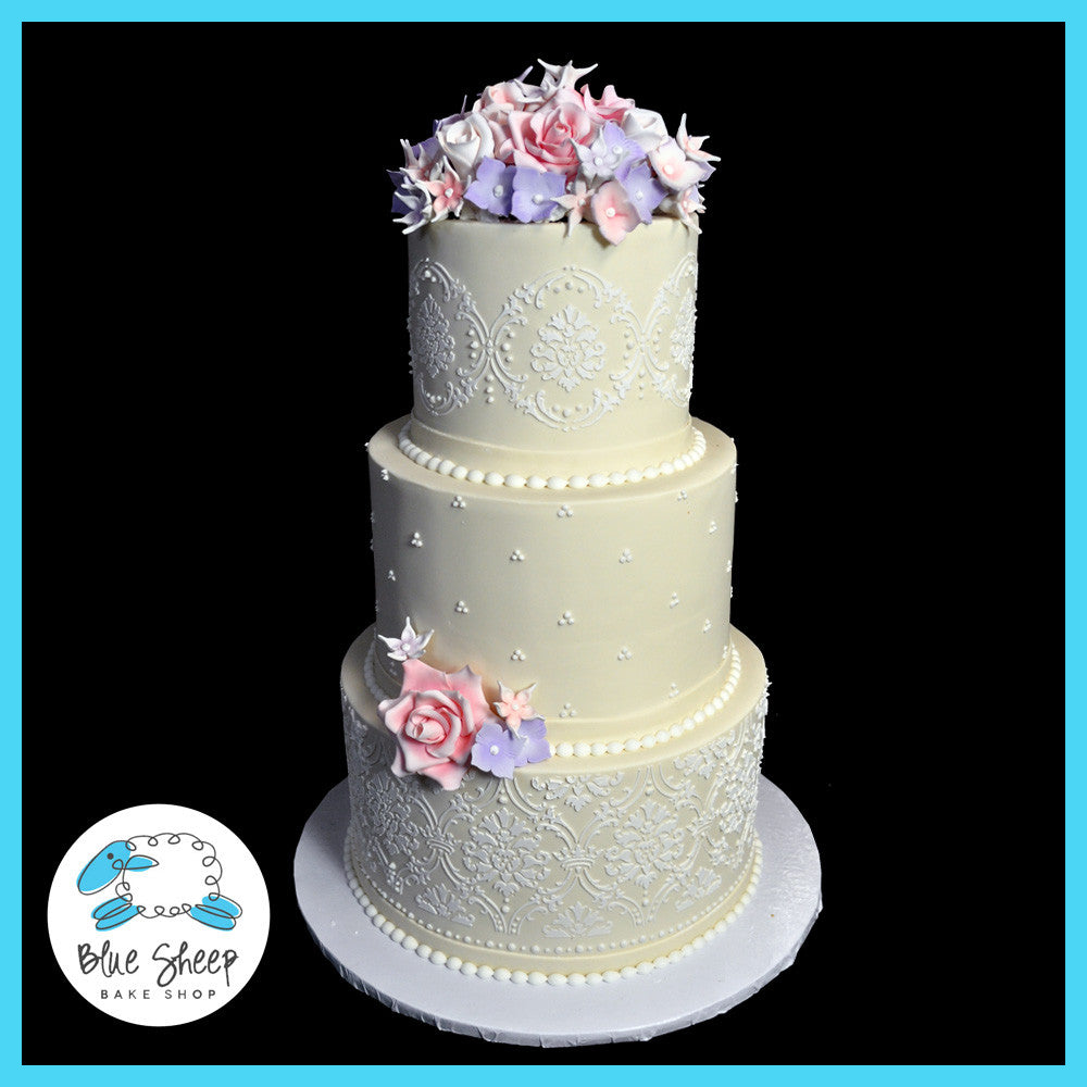 three tiered wedding cake with sugar flowers and lace
