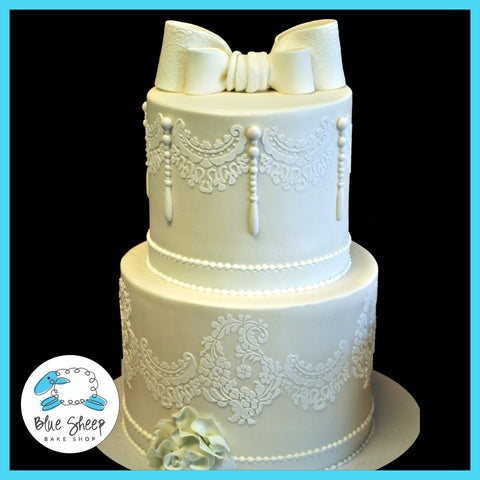 white lace wedding cake with pearls and bow