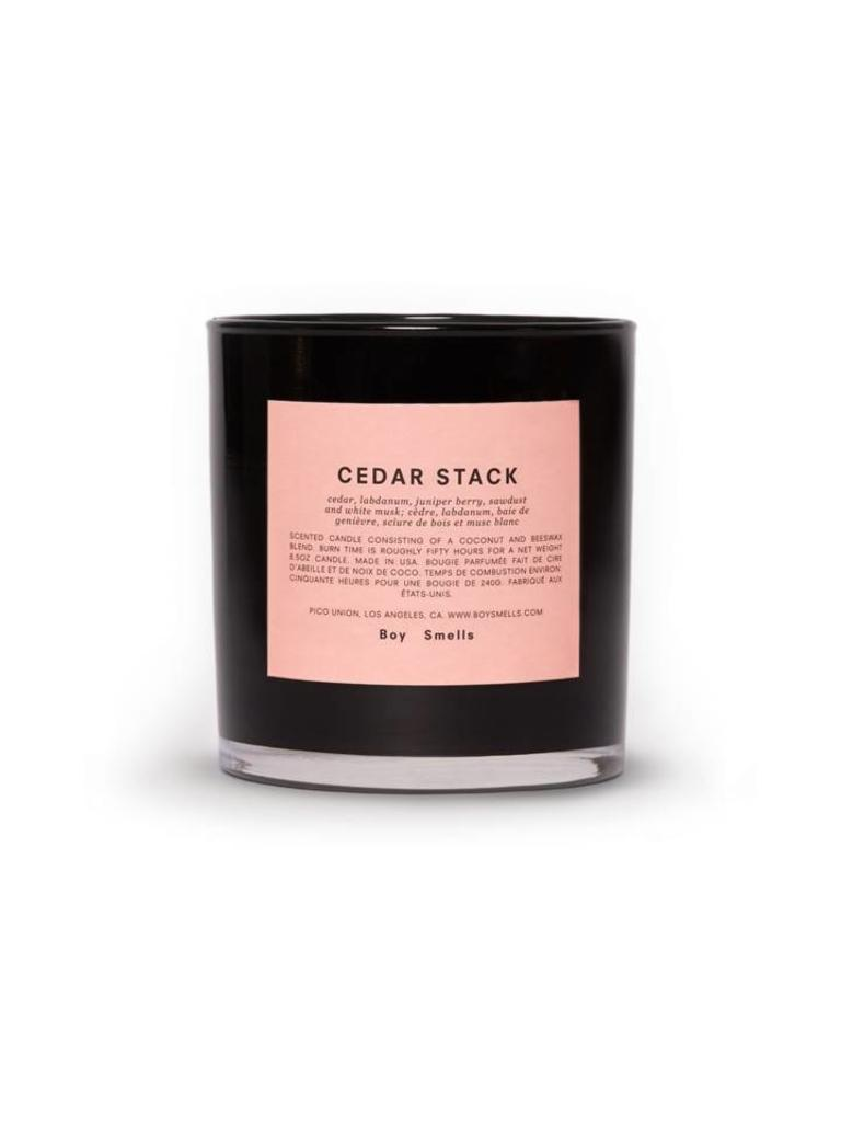 boy smells candle cedar stack