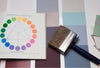 A color wheel beside a paint brush.