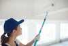 A woman wearing a dark blue ballcap, using a long paint roller to paint a ceiling white.