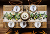 Aerial view of a wooden dining room table with green leaves and white and gold plates and a frosted cake.