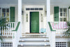 View of the front of a house with a white porch, a green door and green window shutters.