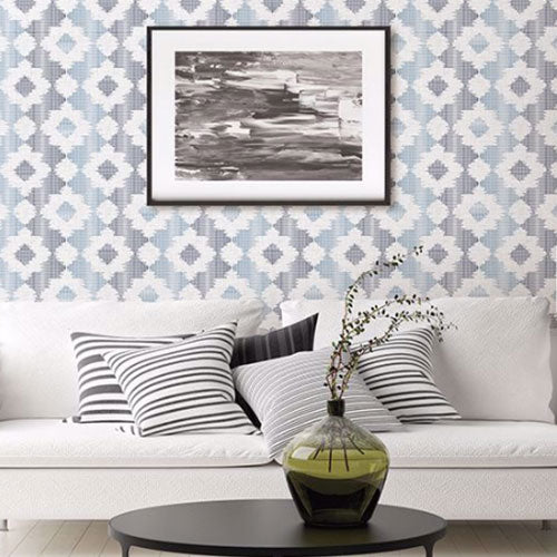 A white couch with black and white pillows in front of a wall with a blue and grey patterned wallpaper from Brewster.