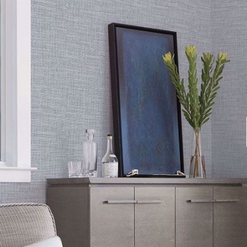 A light brown dresser with a tall green plant in a clear vase and a dark blue print in a black frame, in front of a wall with light blue wallpaper by Brewster.
