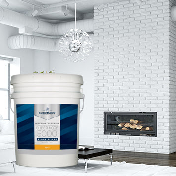 Interior of a living room painted white, with a fireplace with white masonry blocks, with an overlay image of a 5 gallon pail of Coronado Super Kote 5000 coating.