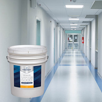 An empty hospital corridor with white walls and a red fire extinguisher on the right-hand side, with an overlay image of a 5 gallon pail of Coronado Super Kote 5000® Tough-Tex Acrylic Knock Down.