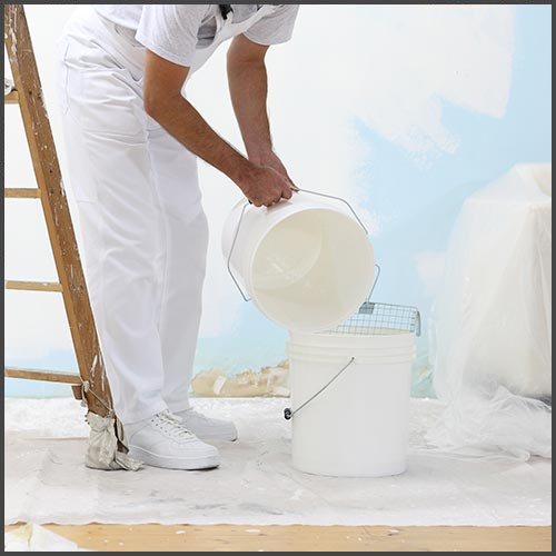 A man wearing white painter's overalls, pouring primer from one white pail into another pail, standing in front of a half-primed wall.