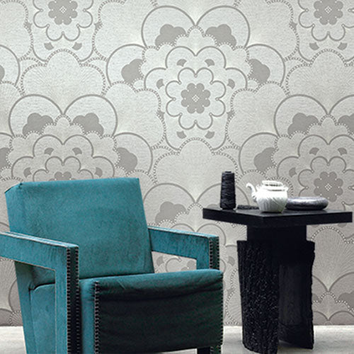 A teal suede chair and black side table, in front of a wall with wallquest wallpaper with a grey floral pattern called