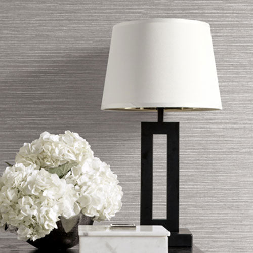 A white bouquet of flowers and a lamp with a white lamp shade, on a table in front of a wall with like grey textured wallquest wallpaper.
