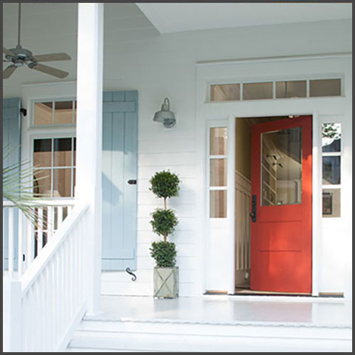 A red front door on a white painted house with light blue painted shutters.