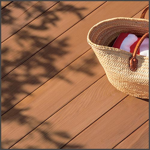 A wooden deck stained with Benjamin Moore's Arborcoat, with a straw beach bag sitting on the deck.