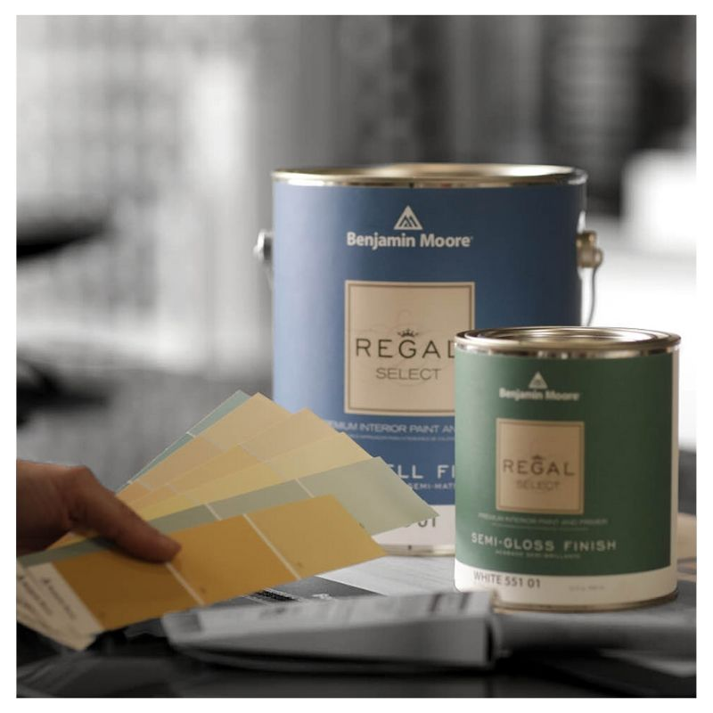 Gallon of Benjamin Moore Eggshell Regal Select next to quart of Semi-gloss Regal Select interior paint and Benjamin Moore color chips