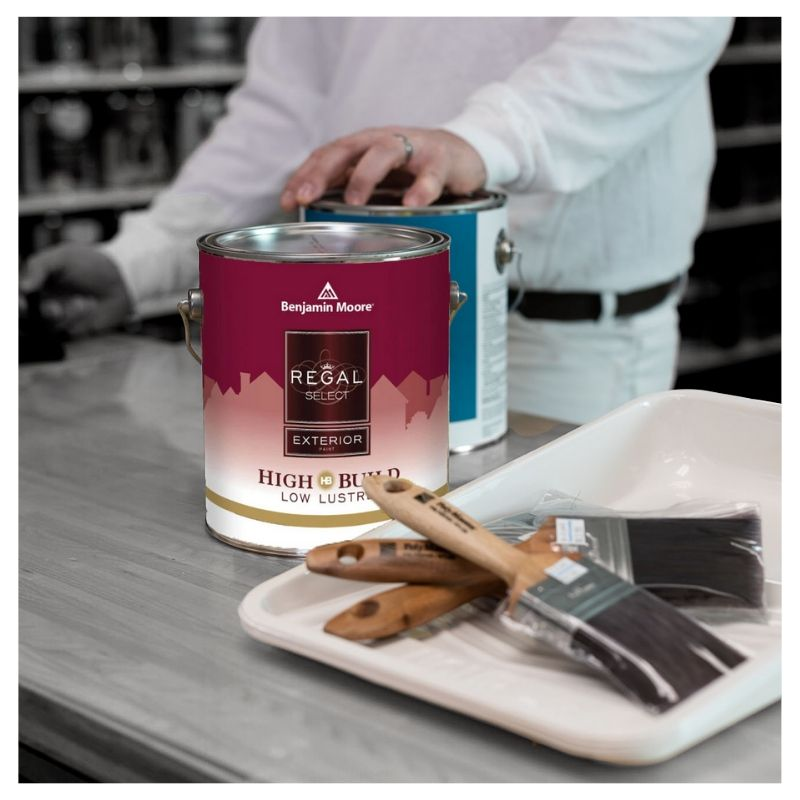 paint contractor at paint store sales counter purchasing a gallon of Regal Exterior Low Lustre Paint, paint brushes, and tray liners
