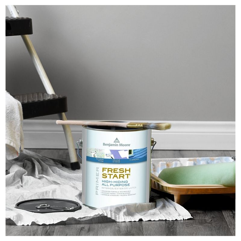 gallon of Benjamin Moore Fresh Start next to paint brush, tray, roller, and step ladder.