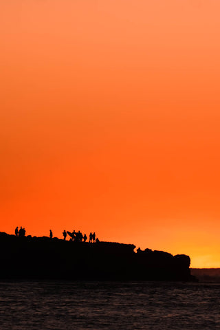 Silhouettes against bright orange sunset at Red Bluff