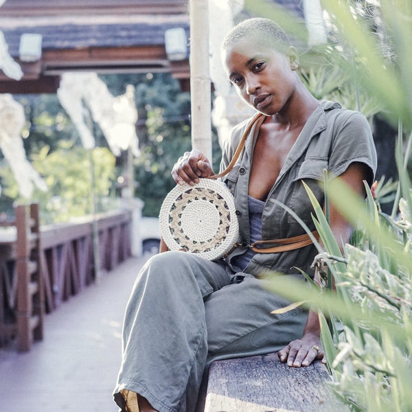 Black Model in Grey Jump Suit posing with White Rattan Crossbody Bag