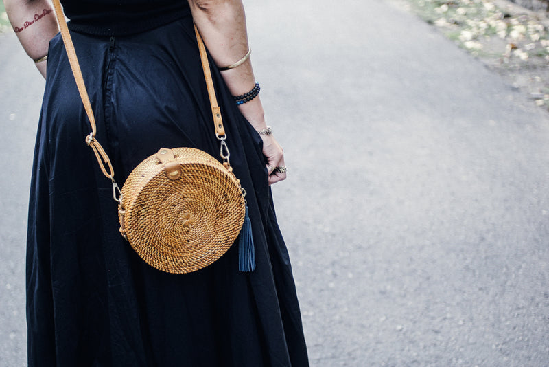 Model in Black Wearing Round Crossbody Bag with Blue Tassel in Street