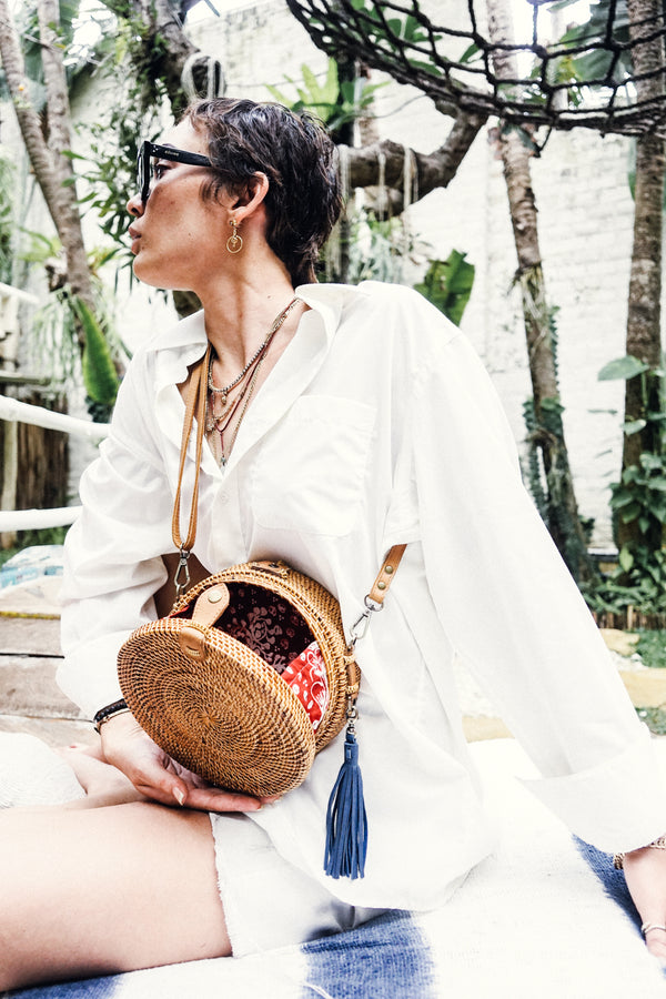 Model in White Top Wearing Handmade Round Crossbody Bag with Leather Tassel