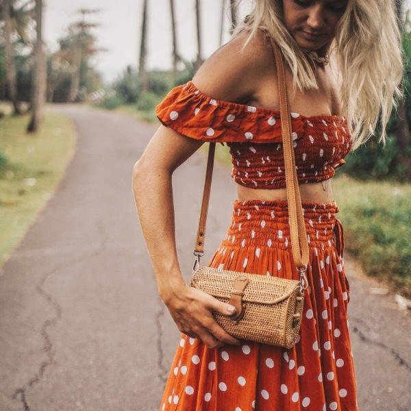 Model in Red Polkadot Dress Carrying Wicker Shoulder Bag