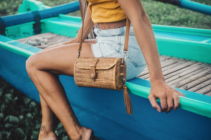 Model in Yellow Top Sitting on Fishing Boat With Crossbody Bali Bag
