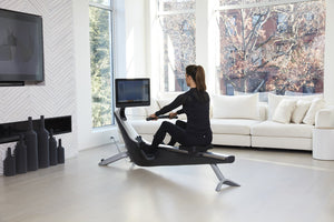 Lady at home working out on a Hydrow Exercise Machine