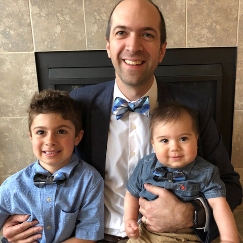 Family wearing blue, silver, and black plaid bow ties for Christmas