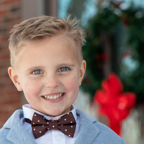 Christmas card photo of a bow wearing brown and white polka dot bow tie