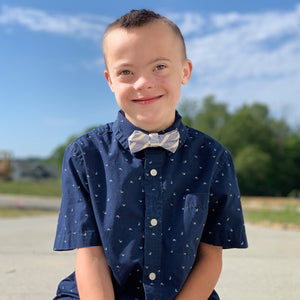 Boy with Down syndrome smiling and wearing a sky blue and white striped linen bow tie in front of a blue sunny sky