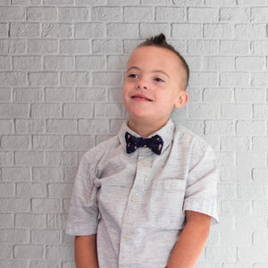 Bow wearing rock emoji bowtie in front of a white brick wall.