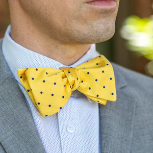 Yellow and blue polka dot bow tie with gray suit outfit