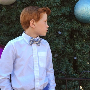 Boy wearing blue and white striped kids size bow tie
