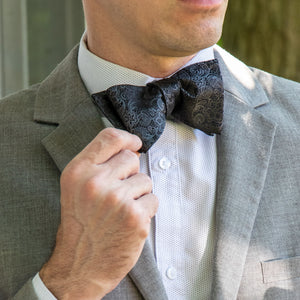 Black paisley woven silk bow tie shown with light gray suit