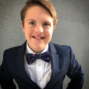 Boy wearing navy bow tie with pink elephants