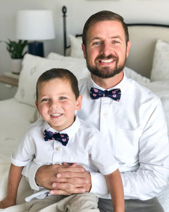 Father and son wearing navy bow ties with pink donuts