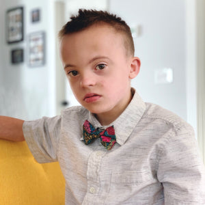 Boy wearing a blue green and pink floral bow tie