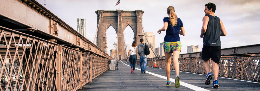 2 people casually running on the Brooklyn bridge