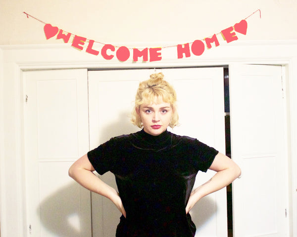 "Photo shows Jenna Knapp (featured artist) standing confidently under a banner that says ""welcome home"" after returning from her hospitalization."