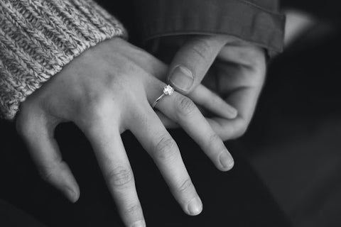 Woman wearing engagement ring with man holding hand